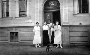 """Detta foto är taget vid Trädgårdsgatan 3. Till vänster om porten syns skylten """"Amanda Nilsson, Syatelier"""". Den tredje kvinnan fr v, stående invid porten, är troligen Amanda Nilsson. Privat ägo."""