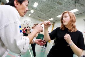 Chefsinstruktören Jessie Cayanan visar Sofie Blomqvist handens rätta vinkel vid slag, rätt vinkel är viktigt för att undvika skador.