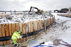 En ram av stålbalkar gör att stockarna runt det som ska bli en ö mitt i sjön står extra stabilt. Ramen av stockar och balkar ska hålla jordmassorna på plats.