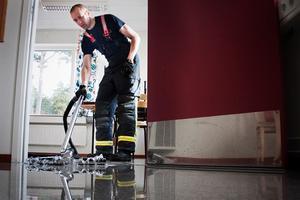 Brandmannen Mikael Andersson försöker suga upp vattnet med en vattensugare.