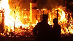 Brandmän ser på när stugan slukas i ett hav av eld.