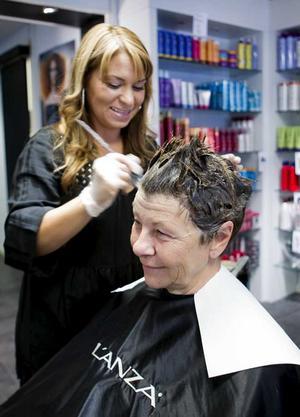 """STEG 2 – FRISYREN. Ulla Persson är en person som bjuder på många skratt, därför tycker vi att det behöver hända något lekfullt i hennes hår.Lena Coskun, på Studio Savoy, börjar med att tunna ut Ullas tjocka hår. Sedan färgas håret i en varm brun färg, och topparna bleks lite för att håret inte ska se lika kompakt ut.Den ena sidan av huvudet klipps jättekort för att få en kul asymmetrisk effekt.Därefter klipper Lena ur Ulla Perssons lugg så att den blir lite """"flikigare"""" och polisongerna klipps fyrkantigt."""