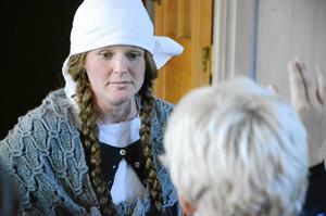 Pigan Stina. Ingela Lindroth har iklätt sig rollen som piga och berättar för eleverna om hennes hemska öde för 200 år sedan.