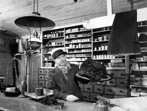15 maj 1964. Det är atmosfär i salig handelsman Thorgrens bod. På bilden agerar Einar Gustafsson lanthandlare av i går. Han bjuder ut en damhatt från sekelskiftet. Den kallades för