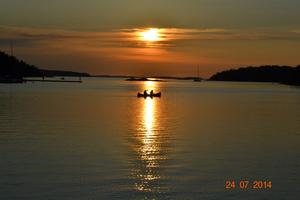 Solnedgång med kanotister över inloppet till Grisslehamns Marina. Foto Clas Munther