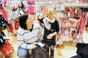 Fyraåriga Ellen Saarenketo håller upp skorna som hon tycker passar bäst till klänningen som mamma Malin håller i.