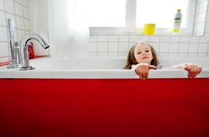"""I det ena badrummet har Roger gjort en knallröd plåtfront till badkaret. Det gillar dottern Cornelia: """"Rött och rosa är mina favoritfärger"""", säger hon."""