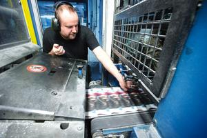 Kollar trycket. Markus Kohtamäki ser till att trycket ser bra ut. Han tar ett exemplar och granskar i kontrollrummet intill.