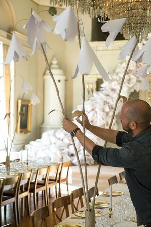 Stylisten och floristen Andreas Graveleij jobbar med pappersblommor i Bergsmanssalongerna.