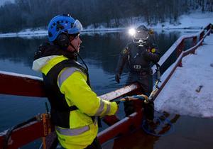Hjalmar Odenstig  förbereder sig för att dyka ner i älvvattnet för att undersöka pontonerna.  Jonas Bosell assisterar på bron.