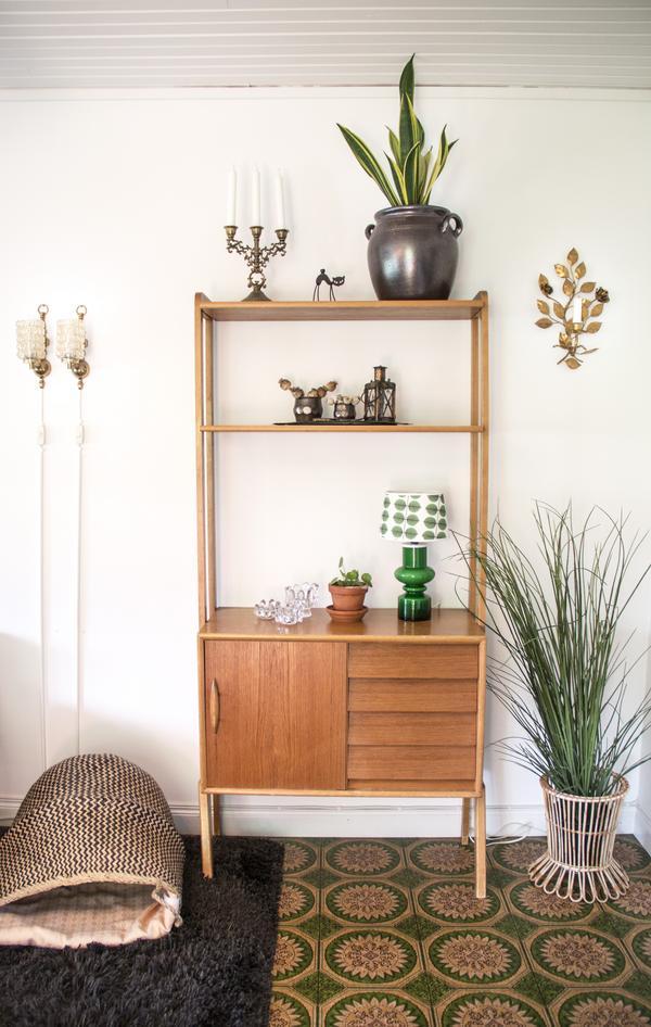 Teakhylla med några godbitar, bland annat en grön lampfot av glas med en stilig Berså-skärm, mönstret är designat av Stig Lindberg.