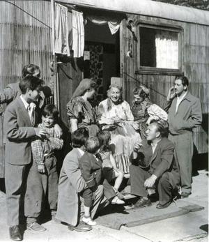 Delar av familjen Taikon samlade utanför Fred Taikons farfars husvagn. Kusinen Fardi håller lille Fred om axlarna.