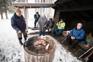 Ryno Jansson, Gun Malmberg och Leif Jönsson njuter av en stunds umgänge med vänner i Riddarhyttans fiskevårdsförening efter vedklyvning och upptakt inför premiären den 3 februari klockan tio.