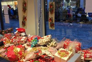 Berg av julklappar sorteras upp på olika bord indelade efter åldrar på barn.