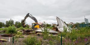 Grävmaskinen hade en enkel uppgift att peta omkull det gamla plåthuset på tomten där det en gång bedrevs skrotverksamhet.