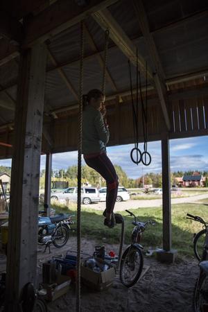 I carporten på gården tränar Elin repklättring.