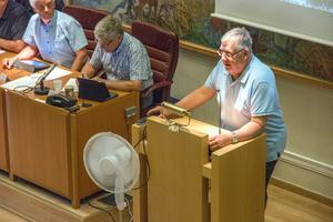 Moderaternas Håkan Freijd (bilden) var en av flera som tog plats i talarstolen när kommunens framtida ekonomi debatterades. Fläkten på stativ gjorde sitt bästa för att vispa runt den kvava luften.