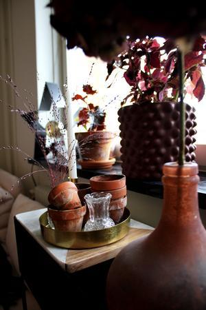 Små jordiga lerkrukor skapar en spännande kontrast mot det guldiga och rosenskära i lägenheten.