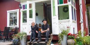 Helene och Dino Holmström på sin favoritplats, trappen. De färgade rutorna i verandafönstret är målade med glasfärg.