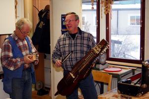 Sven-Erik Håkansson spelar en trudelutt på sin egenhändigt tillverkade nyckelharpa för Jan Danielsson i snickarboden i Nolby.