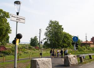 En översiktsbild på Rosa Svenssons plats. Här finns skyltar, en informationsskylt om Rosa Svensson och en bänk att sitta och vila på. Gräs har även såtts vid platsen.