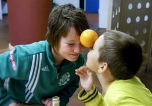 Svårt. Emma Lindin Bäcklund och William Lindin Bäcklund kämpar för att frakta en apelsin mellan sina pannor.