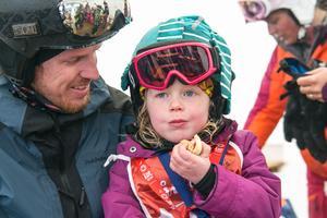 Elicia Nylund gillar att åka skidor, särskilt slalom. Med pappa Henric Nylund värmde hon sig med en varmkorv med bröd i serveringstältet nära målet i Ullådalen.