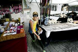 Lena Eliasson smiter in mellan marknadsstånden och plockar kontrollen (kolla till vänster, bakom strumporna). Den 5 juli springer hon VM-sprinten i Venedig.