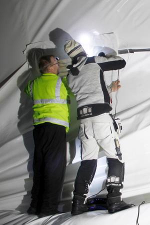 Mikael Bergvik, Jonas Nilsson jobbade med reparationer av tältduken – den stora revan fick lagas bit för bit.