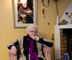 En av Hervor Sjödins favoritplatser därhemma är vid den öppna spisen. Ovanför hänger ett porträtt av maken Nicke Sjödin.