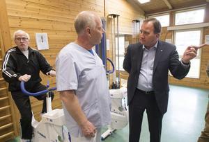 Statsminister Stefan Löfven (s) i samtal med fysioterapeut Håkan Kvist under dagens besök på Hofors hälsocentral. I bakgrunden cyklar Jan Olov Tegnander.Foto: Fredrik Sandberg / TT