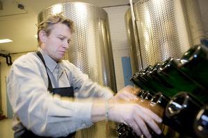 Arkivbild från 2008, Peter Mosten vrider flaskorna för hand i lagringsställ. Den här processen sköter hädanefter en robot.