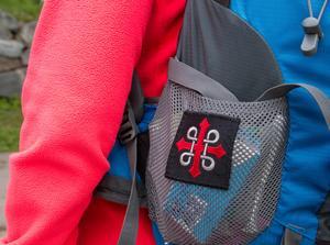 St:Olofskorset med det grå St:Hanskorset inflätat är den officiella markeringen längs de pilgrimsleder som går mot Nidaros/Trondheim. Kristina har symbolen på sin ryggsäck.