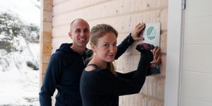 Jörgen Wallin och Sandra Holmström sätter upp beviset på att deras fritidshus är Svanenmärkt.