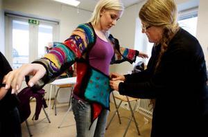 Brorsdottern Evelina Pellving hjälper till att packa upp och ångstryka allt inför utställningen. Hon får också vara mannekäng och visa upp Siv Annelis sjalkoftor och andra färgstarka plagg. Foto: Ulrika Andersson