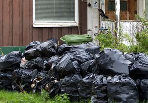 Ett stort antal sopsäckar med tomma kattmatsburkar ligger på tomten.