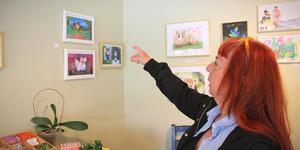 Yvonne Svensson framför sina elevers tavlor. Utställningen som heter