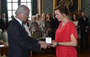 Tilde Björförs tar emot H.M Konungen Medalj av 8:e storleken i högblott band ur kungens hand. Arkivfoto: Anders Wiklund/TT