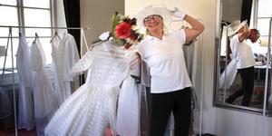 """Med en hatt från 1930-talet, klänning från 1960-talet och bukett från 1990-talet demonstrerar Ulla Pedersen bröllopsaccessoarernas tidsresa. """"Under kriget var det inga pärlor, kvinnorna kunde i stället gifta sig i sin lottauniform"""", berättar hon."""