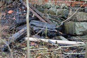 Nedanför huset ligger svartbrända stockar från överbyggnaden.