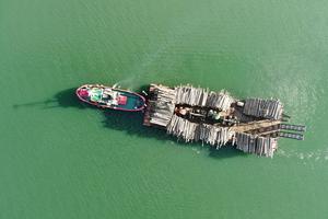 En pråm transporterar virke från öar till fastland. Många öar har helt ändrat profil efter att stormen Alfrida härjade i januari. Foto: Henrik Ismarker/Spillersboda flygfoto