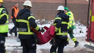 Brandmän släpar ut en docka. I bakgrunden syns ambulanspersonal som är beredda på att ta över arbetet.