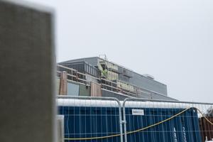 Byggarbetare klättrar på taket. Inom några månader ska man vara klar.