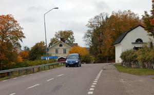 Vid kyrkan är det trångt då en mindre byggnad står alldeles intill Landsvägen.