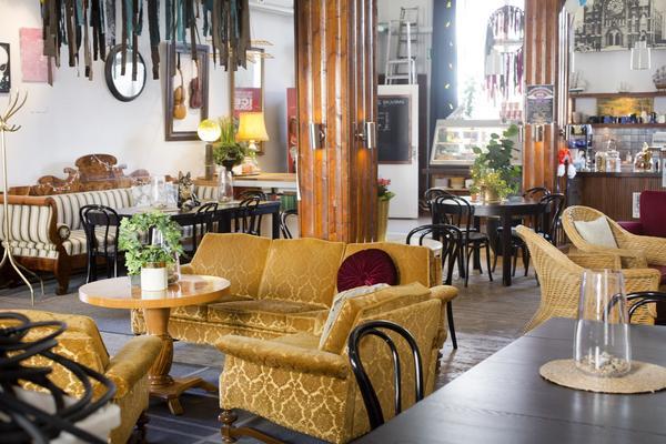 Från entrén ser man rakt in i kaféet. Möblerat med en ombonad mix av stilar.