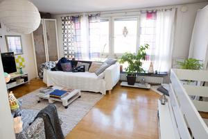 Lastpall som soffbord och vida fönster i vardagsrummet en trappa upp.