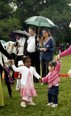 Midsommar i Strömsholm. Sindi Rösby, 3 år, och Johanna Knitsh, 2,5 år, deltog i dansen kring midsommarstången i Strömsholm trots att regndropparna föll. Foto: VLT:s arkiv