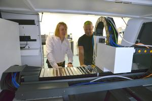 Tim Smith och Peter Danielsson tittar på en lasermaskin som är klar för leverans.