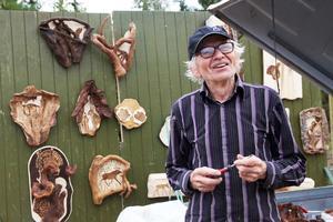Konstnären Berndt Persson och i bakgrunden hans konst.