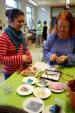 Basma Juzel gör ett armband av pärlor och får hjälp av Eva Springe. Foto: Carin Selldén